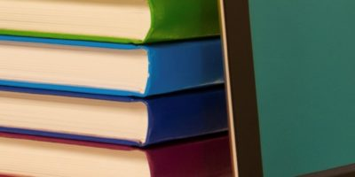 Stack of colorful books and electronic book reader in the book shop